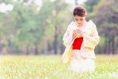 Asian young girl kimono. Asian young girl wearing a kimono in natural green grass Royalty Free Stock Photos