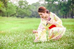 Asian young girl kimono. Asian young girl wearing a kimono in natural green grass Royalty Free Stock Images