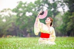 Asian young girl kimono. Asian young girl wearing a kimono in natural green grass Stock Photo
