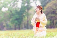 Asian young girl kimono. Asian young girl wearing a kimono in natural green grass Stock Image