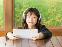 Asian young girl is listening to music through headphones Stock Photo