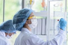 Asian young girl student scientist researching  and learning in a laboratory. Background beaker biology biotechnology black blue chemical chemist chemistry royalty free stock photos