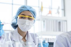 Asian young girl student scientist researching  and learning in a laboratory. Background beaker biology biotechnology black blue chemical chemist chemistry royalty free stock image