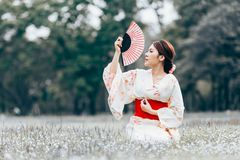 Asian young girl kimono. Asian young girl wearing a kimono in natural green grass Royalty Free Stock Photography