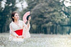 Asian young girl kimono. Asian young girl wearing a kimono in natural green grass Royalty Free Stock Image