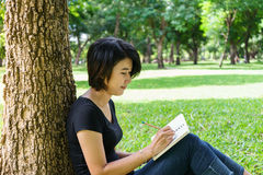 Asian young girl write letter under the tree Stock Photo