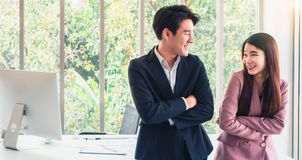 Asian young handsome business man talk with business woman so funny. Good relationship in working. Causing a good atmosphere at stock photos