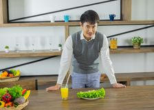 Asian young healthy man, stand at the dining table in the kitchen royalty free stock image