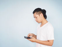 Asian young hipster man wear white t-shirt playing mobile phone. Over light blue wall background Stock Image