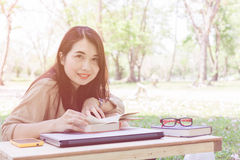 Asian young lady read book at outdoor in park Stock Photos