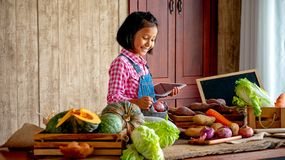 Asian young little girl with smiling use tablet to check the list of various vegetable on table in the kitchen royalty free stock image
