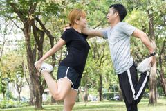 Asian young love couple workout on stretching their bodies together to be prepared for the exercise. Asian young love couple workout on stretching their bodies royalty free stock photography