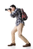 Asian young male backpacker take a picture. Full length portrait isolated on white Royalty Free Stock Images