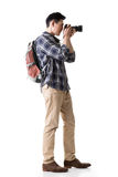 Asian young male backpacker take a picture. Full length portrait isolated on white Royalty Free Stock Photo