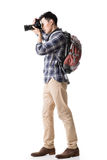 Asian young male backpacker take a picture. Full length portrait isolated on white Royalty Free Stock Image