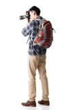 Asian young male backpacker take a picture. Full length portrait isolated on white Stock Image