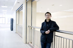 Asian young man. Stands by banister in a modern house Royalty Free Stock Image
