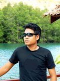 Asian Young Man. An asian  youngman wearing sun glass and standing by the sea and mangrove forest as background Royalty Free Stock Photography