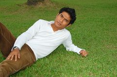 Asian Young Man. Portrait of an asian young man lying on the grass Royalty Free Stock Photos