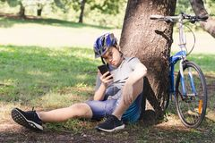 Bicycle. Asian young man bicycle standing by tree and listening to music with earphone Stock Images