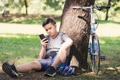 Bicycle. Asian young man bicycle standing by tree and listening to music with earphone Stock Image