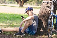 Bicycle. Asian young man bicycle standing by tree and listening to music with earphone Stock Photography