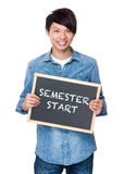 Asian young man with chalkboard showing phrase of semester start Royalty Free Stock Photo