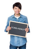 Asian young man with chalkboard showing a word scholarship Stock Image