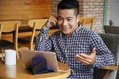 Using internet at cafe. Asian young man communicating online using his tablet at coffee shop royalty free stock image