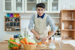Asian young man is cooking,Portrait of young man looking recipe. On laptop while cutting broccoli on board in the kitchen Stock Image