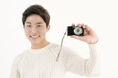 Asian young man with digital camera Royalty Free Stock Photos