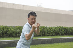 Asian young man display Chinese KongFu. Or young Man In a Fight. Business concept Stock Images