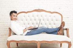 Asian young man looking at camera while sitting relax on sofa an Stock Photography