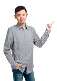 Asian young man pointing aside Stock Images