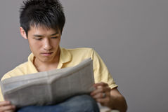 Asian young man reading newspaper Stock Photography