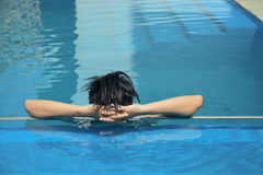 Asian young man relaxing on a swimming pool Royalty Free Stock Photo