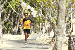 Asian young man running on the alley with trees alongside, Sport Royalty Free Stock Photos