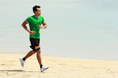 Asian young man running on beach, Sport concept Royalty Free Stock Photography