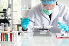 An asian young man scientist using mechanical scale. An asian chemist or scientist researcher using mechanical scale for gathering and measuring specimen at stock images
