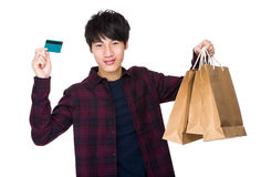 Asian young man with shopping bag and credit card Royalty Free Stock Photo