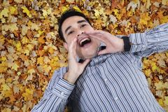 Asian young man shouting on leaves Stock Photo
