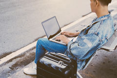 Asian young man sitting on the chair at the airport bus stop and Stock Photography