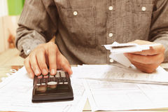 Asian young man sitting on home office using calculator and calc Stock Photography