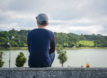 Asian young man sitting and looking at the lake Stock Photography