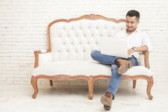 Asian young man sitting relax on sofa while working on laptop at Royalty Free Stock Photography
