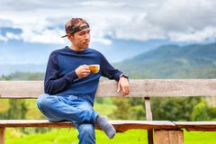 Asian young man smiling with hat sitting on a wooden bench and holding coffee cup in morning time at green terraced rice field in. Pa pong pieng , Mae Chaem Royalty Free Stock Photo
