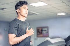 Asian Young man in sportswear running on treadmill at gym | Healthy activity sport royalty free stock photos