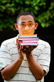 Asian young man with stack of books on hands Stock Image