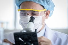 Asian young man student scientist researching  and learning in a laboratory. Background beaker biology biotechnology black blue chemical chemist chemistry clean royalty free stock photo