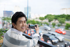 Asian young man taking photo of city street from the balcony. Stock Images